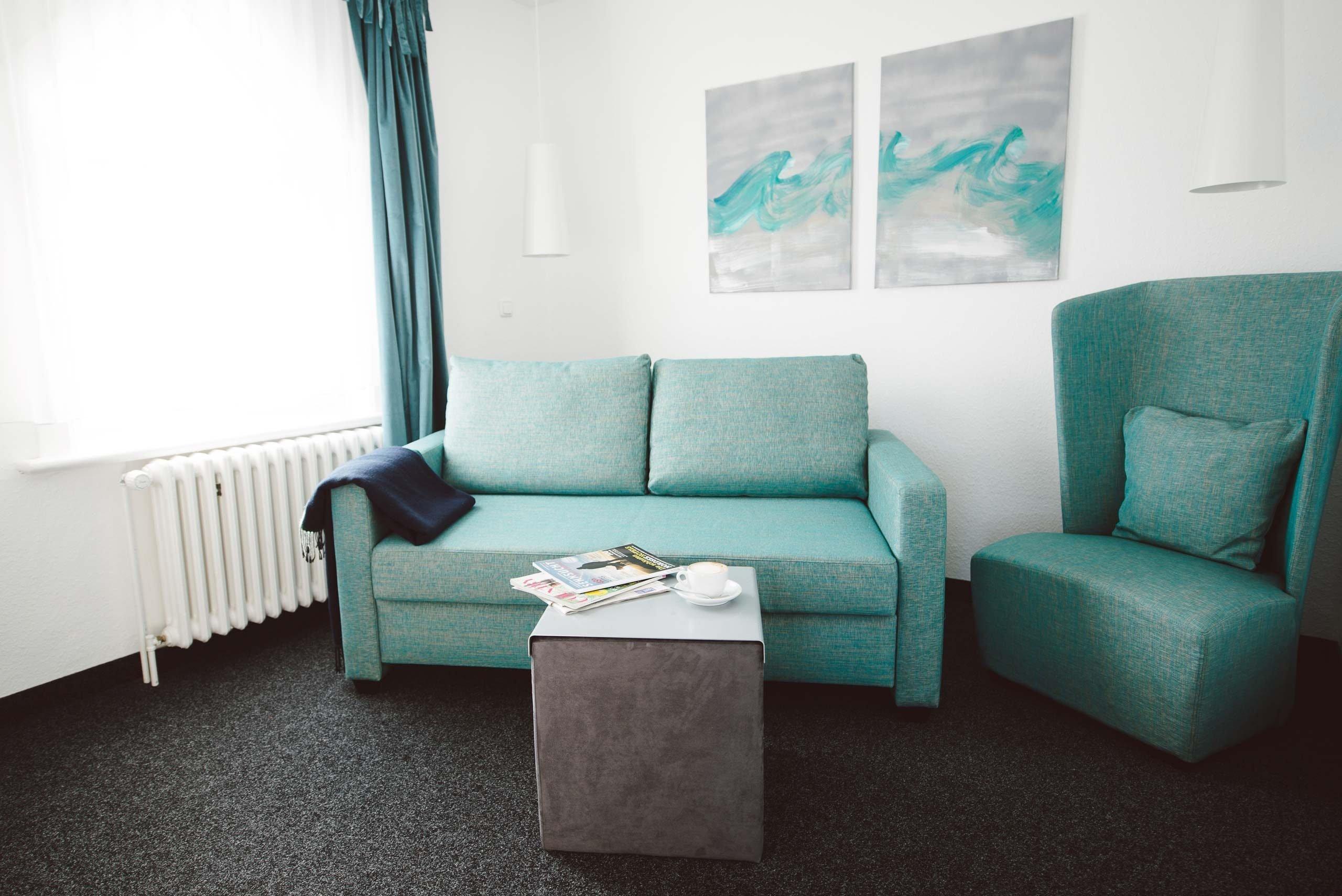 XL Zimmer: Sofa in einer Juniorsuite im meerzeit Hotel in Cuxhaven